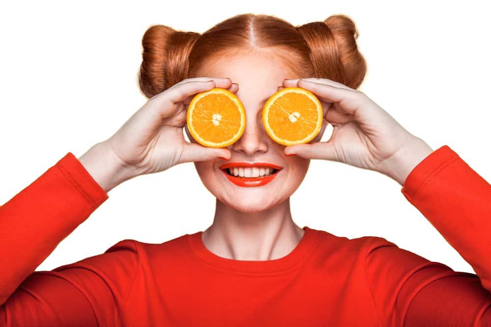 mujer con fruta de naranja