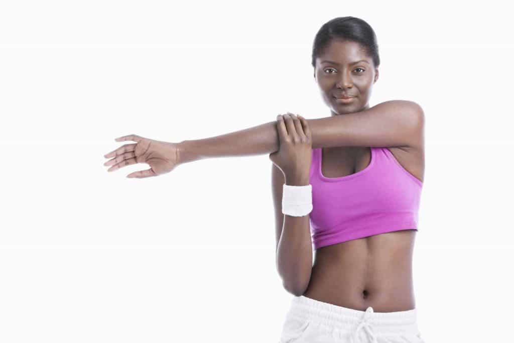 Une femme étire les muscles de ses épaules