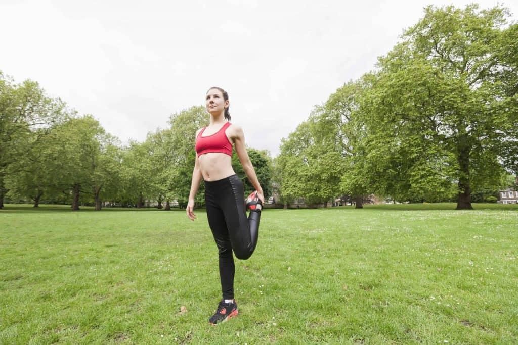Une femme étire ses quadriceps