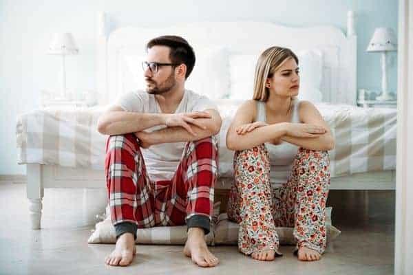 een man en een vrouw zitten bij het bed