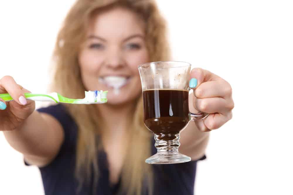 uma mulher com um café e uma escova de dentes