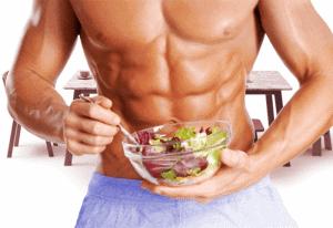 A muscular man eats a salad