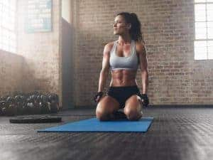 woman kneeling on an exercise mat