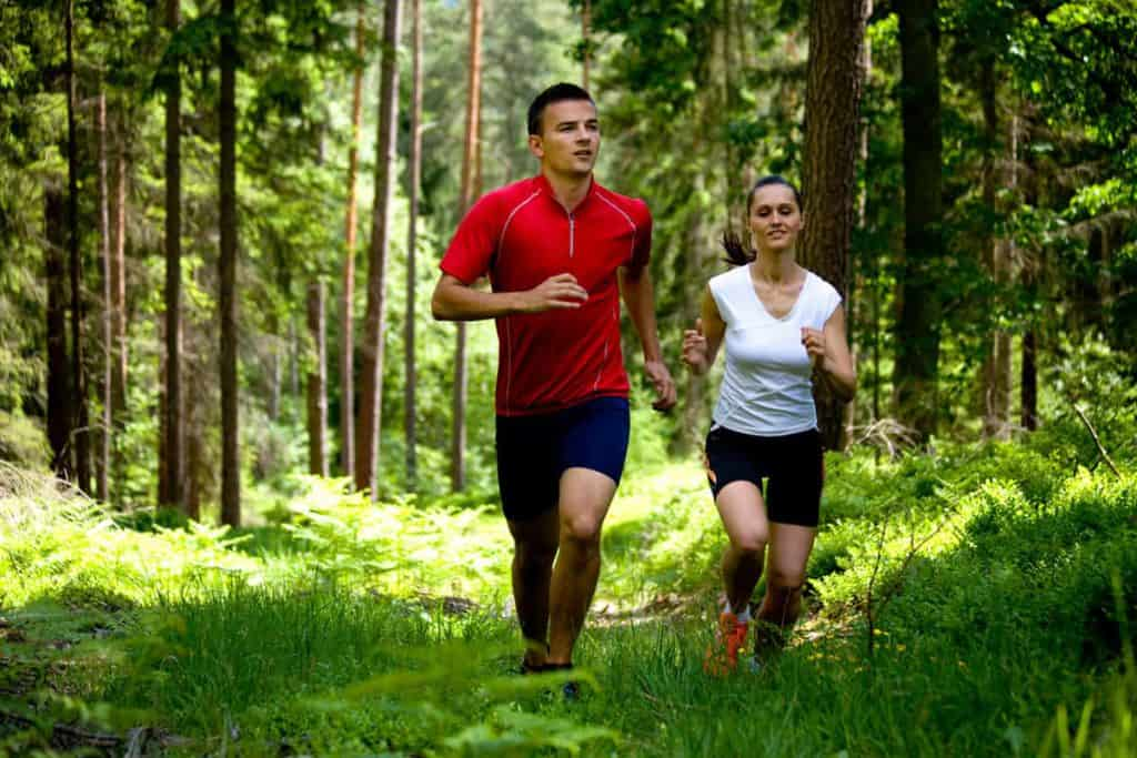 a man and a woman run in the woods