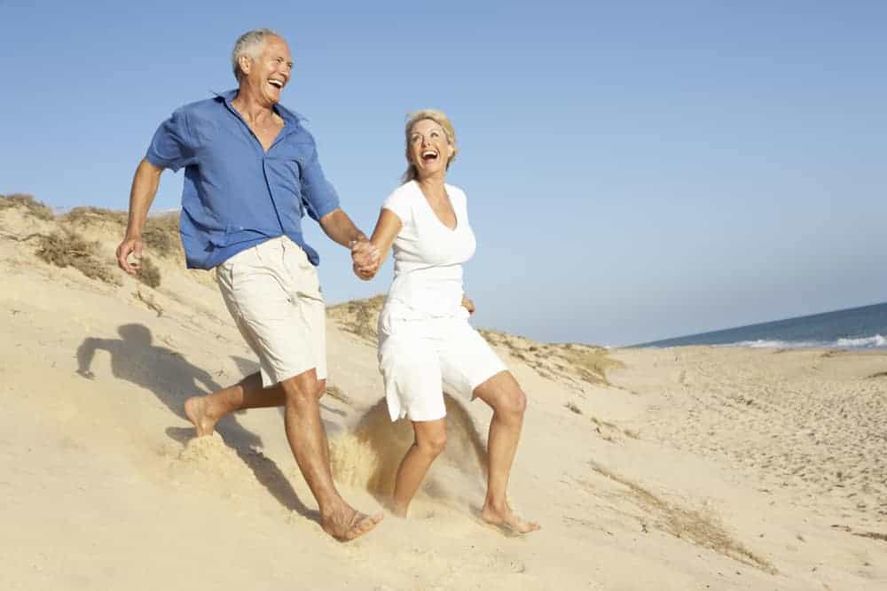 a man and a woman are running on the beach