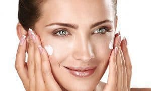 a woman lubricates her face with a cream
