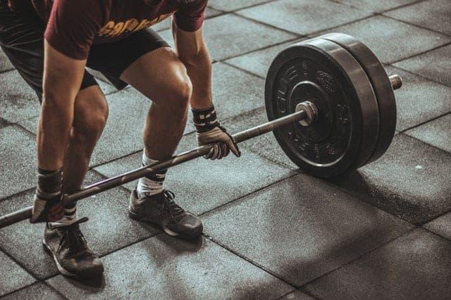 man lifting barbells