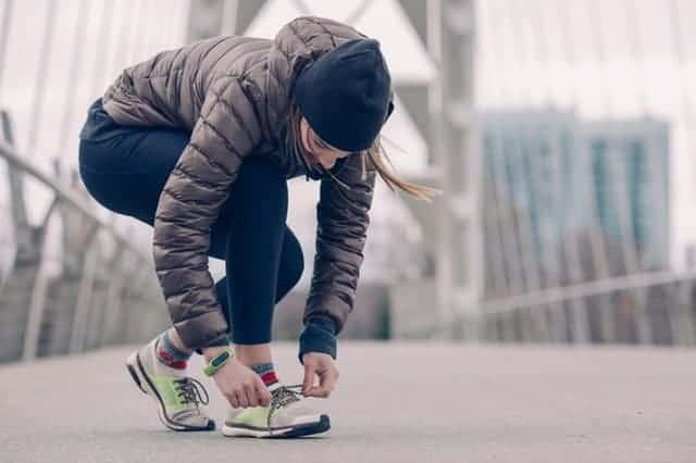 a woman ties her shoe