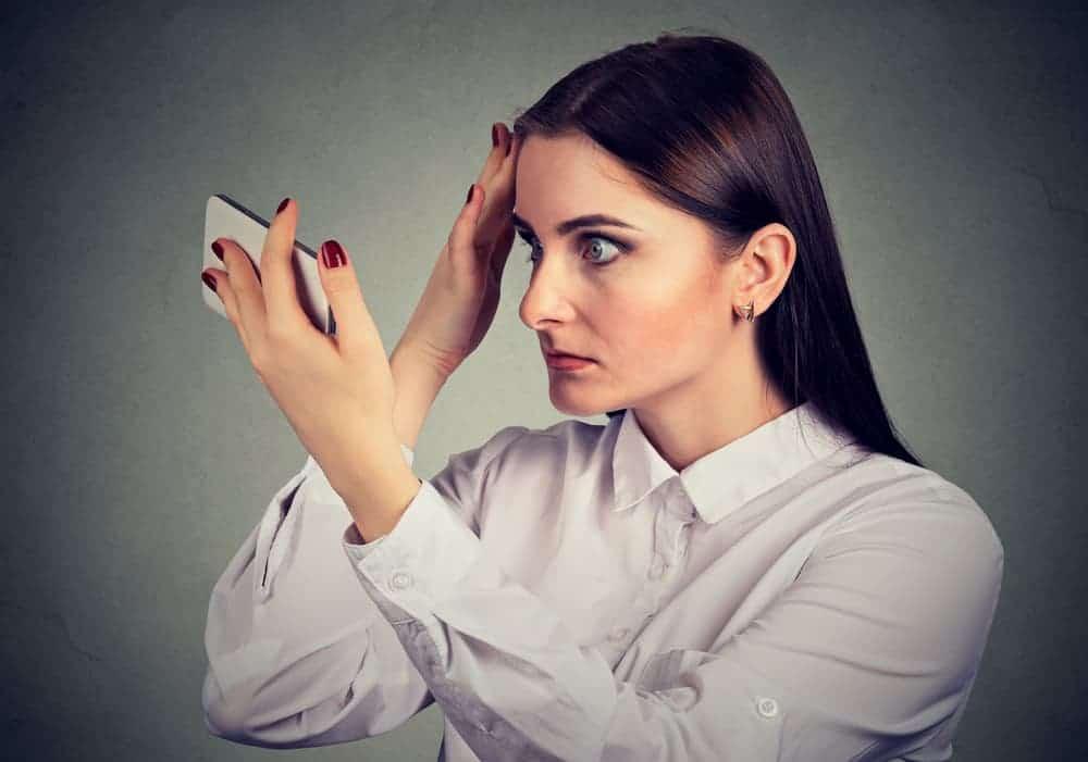 a woman checks her hair