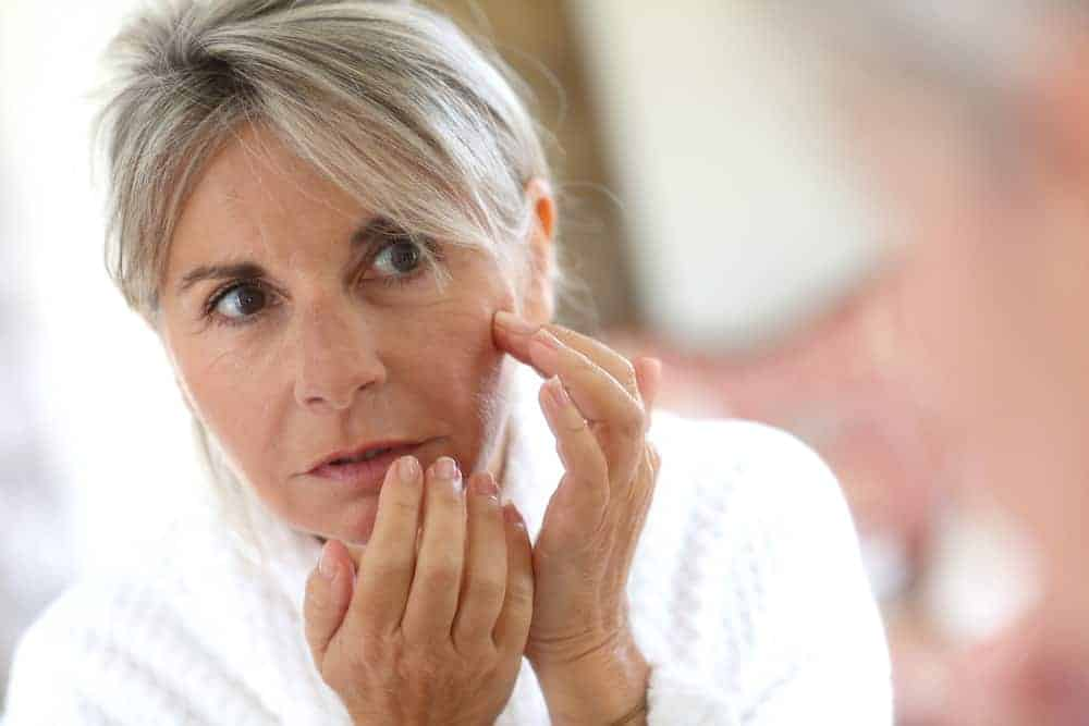 a woman looks at wrinkles